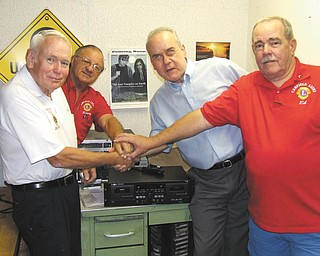 Using a symbolic gesture to represent a partnership of three decades between Canfield Lions Club and Youngstown Radio Reading Center are, from left, Ted Filmer, Lions past district governor; Harry Pancher, Lion; Mike Bosela of the center; and Ed Ellis, Lion. The club recently bought a new cassette recorder for the center to replace old equipment. The center broadcasts articles specifically for the sight impaired; Linda Ellis is a reader. Other Lions involved in the presentation were Marilyn Schmidt and Joan Filisky.