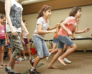 (L-R) Rita Sulebi, 12,  Lianna Sulebi, 8, and Ranean Sulebi, 9, all of Boardman, Ohio, run to collect eggs without being hit by a ball. A couple different versions of the 'Live Pacman' game were played at the Boardman Library on August 9, 2012.