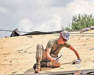 Ian Evans works on a roof at Seven Ranges Scout Reservation during a project brought together by three branches of service.
