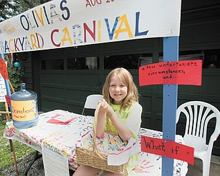 """Olivia Helmick's smile, as she sits at the booth announcing Olivia's Backyard Carnival, seems to say """"come on over"""" Sunday to her house at 8793 Woodland Road, just off Arrel Road and state Route 170 in Poland Township, and enjoy the fun and help homeless people at the same time."""