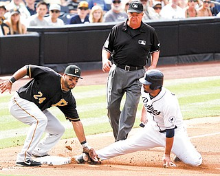 San Diego Padres' Carlos Quentin, right, is tagged out by Pittsburgh Pirates third baseman Pedro Alvarez, left, as umpire Joe West moves in to make the call during the first inning of Wednesday's game in San Diego.