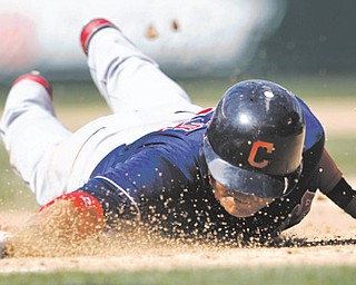 Cleveland Indians' Shin-Soo Choo dives safely back to first base on a pick-off attempt in the eighth inning of Wednesday's game against the Mariners in Seattle.