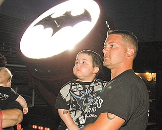 Jayden Barber, 4, and his father, Tim Barber, look into them sky at a helicopter that was drawn to the Boardman High School football field by the Bat Signal behind them.