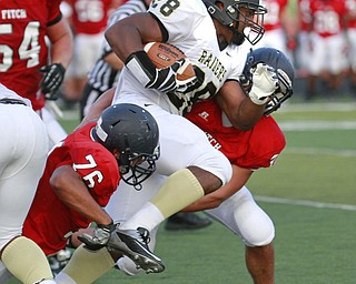 ROBERT  K.  YOSAY  | THE VINDICATOR --..Hardings #28 LeShun Daniels is tripped up at the line by #76 Fitch  Tony Behanna  and hidden is Fitch's 36 C J Martini -First Quarter Action.. Warren Harding @ Austintown Fitch -Fitch Stadium...(AP Photo/The Vindicator, Robert K. Yosay)