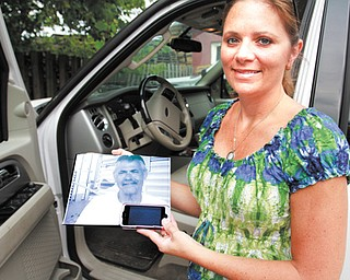 Tina Yanssens holds a picture of her father, Dave Muslovski, who was 55 when he was killed by a driver who was texting. Yanssens and her family lobbied for a texting-while-driving ban in Ohio. One targeting young drivers takes effect Friday.