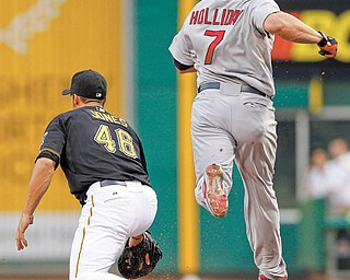 St. Louis Cardinals' Matt Holliday (7) beats out an infield single as Pittsburgh Pirates first baseman Garrett Jones gets the late throw in the first inning of the baseball game Monday in Pittsburgh.