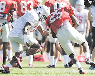 Ohio State linebacker Ryan Shazier, left, tackles running back Bri'onte Dunn at practice. There is a nagging feeling clinging to the Buckeye defenders that they somehow let everyone down last season. So this season, they feel they owe everyone — the team, the fans, and college football in general — a little bit of payback.