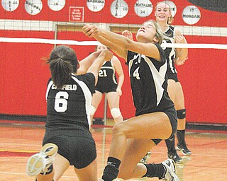 Canfield's Anastasia Cook (6) and Jacqueline Cook (4) converge on the ball during a volleyball game Thursday against Girard at Canfield High School. The Cardinals downed the Indians, 3-1.