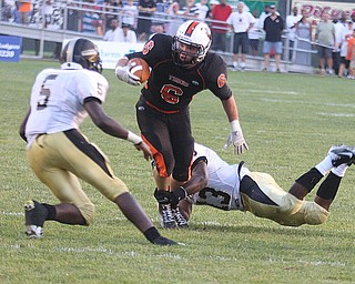 NICK MAYS l THE VINDICATOR.(6) Tyler Drass of Howland tries to get away from (13) Lebrandon Watson as (5) Lyndal Kimble comes up to help during the first quarter in Howland. - harding vs howland at howland  Friday 08312012