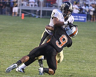 NICK MAYS l THE VINDICATOR.(9) Trey Bryarly of Howland makes the tackle as (2) Jalyn Powell tries to get away during the second quarter in Howland. - harding vs howland at howland  Friday 08312012