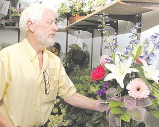 Gary Doles, owner of Bloomin' Crazy Florist, looks over an arrangement at his Boardman business. Doles said every business, including those online, should have to pay sales tax.