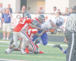 Hubbard's Larry Scott (3) is stopped by Girard defenders during their game at Girard on Friday.