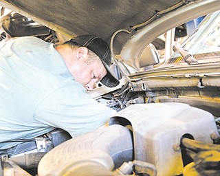 Ray Kelly, a Mahoning County mechanic, works on the engine of a county vehicle at the sanitary engineer's office, 761 Industrial Road, Youngstown, where fueling and maintenance are centralized to save money.