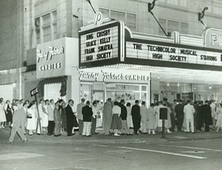 VINDICATOR FILE PHOTO...The Paramount Theater, downtown Youngstown, reopened in the former Liberty Theater in July 1929 when the city had a bustling downtown anchored by two major department stores, a host of other retail shops and several theaters. This 1956 line to get into the West Federal Street theater stretched around the corner past Fanny Farmer Candies onto Hazel Street. In the hey-dey of motion pictures, block-long queues were standard at all the downtown theaters most Saturdays and Sundays.