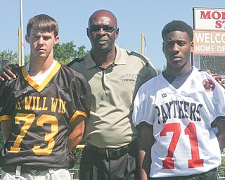 Warren G. Harding players Jimmy Rumple, left, and Lamar Carmichael, right, flank Raiders coach Steve Arnold while wearing the throwback jerseys the team plans to wear in upcoming games. Harding will wear the Western Reserve jersey Rumple is wearing on Oct. 12 against Cleveland Heights. The Raiders will wear Carmichael's WGH jersey on Oct. 19 against Bedford.