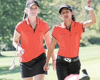 Canfield's Michelle Whiteleather, left, and Lianna Tucci talk as they walk during their golf match against rival Poland on Wednesday at Diamond Back Golf Course in Canfield. The Cardinals defeated the Bulldogs, 175-194.