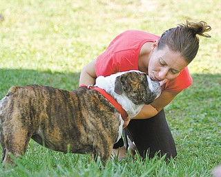 Mary Gump of Youngstown receives a kiss from Mabel at her home on the city's West Side. The bulldog was reported stolen at the Bob Evans restaurant along Belmont Avenue on Aug. 14. Gump helped in the dog's recovery and is housing Mabel until her owner, Brook Jillings of Boise, Idaho, arrives and reunites with her beloved pet sometime today.