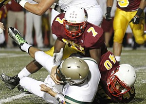 ROBERT  K.  YOSAY  | THE VINDICATOR --..SACKED  is #13 svsm  Clayton Uecker behind the line by  #7 CM Marlan Everson and#40  Todd Thorton - second  quarter action ---Akron St Vincent St Mary @ Cardinal Mooney  at YSU Stadium..(AP Photo/The Vindicator, Robert K. Yosay)