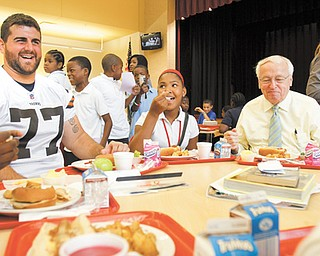 John Greco, left, a Cleveland Browns offensive lineman and Boardman native, and Kevin Concannon, the United States Department of Agriculture food and nutrition service undersecretary, eat lunch with Calayla Abron, a seventh-grader at Youngstown's Wilson Middle School. Concannon joined Wilson students for lunch Tuesday to talk about the new guidelines for school lunches, which require healthier options.
