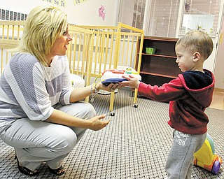 Holly Metzinger, administrative director at Great Expectations Learning Center in Hubbard, shows a toy to 1-year-old Brayden Frazzini. The learning center had an open house Tuesday night so families could see its new location for toddlers and infants.