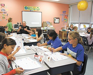 Fifth-graders at Frank Ohl Intermediate School in Austintown work with Jeff Toth, township police officer, during their Drug Abuse Resistance Education class. A portion of the state's school report cards was released Wednesday, and the district met 26 of 26 performance indicators. Fifth-grade test scores have been the most difficult to raise, but they met state specifications this year.