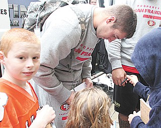 Autograph seeker Kyle DeBucci, left, of New Middletown waits his turn for an autograph from 49ers tight end Garrett Celek outside the Boardman Holiday Inn on Wednesday.