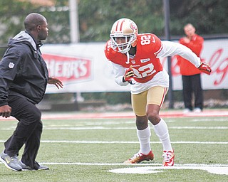 San Francisco 49ers wide receiver Mario Manningham (82), of Warren, participates in a drill during practice Wednesday at Stambaugh Stadium. Assistant coach Ejiro Evero, left, watches.