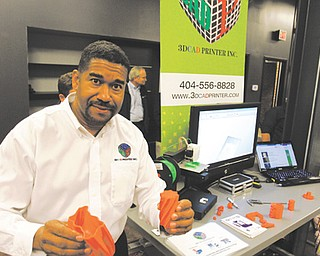 Ron Robinson, president and chief executive of 3DCAD Printer Inc., shows off some of the products made using the additive manufacturing process. Robinson joined several other private companies and universities Thursday at the opening of the National Additive Manufacturing Innovation Institute at 236 W. Boardman St.