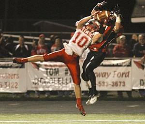 ROBERT  K.  YOSAY  | THE VINDICATOR --..Breaking up the pass and intercepting in the endzone is Niles #10  Chris Parry as the pass was intended  for #11  Jake Dawson -  during third quarter action Niles at Canfield - Bob Dove Field ..(AP Photo/The Vindicator, Robert K. Yosay)