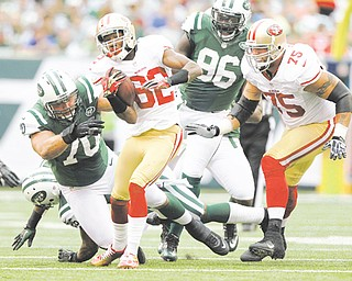 San Francisco 49ers wide receiver Mario Manningham (82) breaks a tackle by New York Jets defensive end Mike DeVito (70) during the first half of Sunday's NFL game in East Rutherford, N.J. The 49ers routed the Jets, 34-0, with Manningham, a Warren native, recording three catches for 47 yards, plus a 28-yard gain on an end-around.