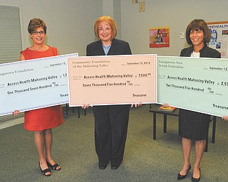 Holding oversized checks totaling a donation of $11,700 to Access Health Mahoning Valley are representatives of area organizations, from left, Janice Strasfeld, executive director of Youngstown Foundation, which gave $1,700; Patricia Brozik, president of the Community Foundation of the Mahoning Valley with a donation of $7,500; and Deborah Grinstein, endowment director for Youngstown Area Jewish Federation, which donated $2,500.  Access Health, a nonprofit organization, provides free health and dental care to poor and uninsured adults in Trumbull and Mahoning counties. Access Health recognized key supporters Sept. 12 at Youngstown City Health District.