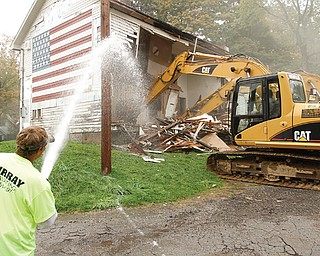 Scott Benbel sprays water to keep down dust as a mechanical shovel demolishes American Legion Post 472 on East Indianola Avenue in Youngstown. If all goes according to plan, a new, one-story ranch-style building will rise at the same location within 60 days to replace the original, which was built in the late 1800s.