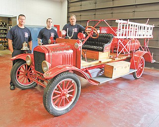 Austintown firefi ghters Dave Schertzer, left, Brian Griffin and Tom Neff stand by the department's 1917 Ford Model T firetruck. They plan to use the truck in parades and event appearances. The truck was donated to the department by Lisa Callahan and Linda Toth, whose father had owned it for 60 years.