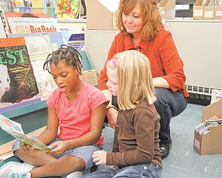 Deborah Walters, a second-grade teacher at E.J. Blott Elementary School in Liberty, helps DeAshya Jenkins, left, and Olivia Decker read a book. Walters recently was nominated as the Ohio Lottery Partners in Education September Teacher of the Month for the Youngstown region.