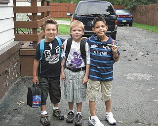 Neighbors Santino, Landon and Christian, all of Boardman, hang out together while waiting for the bus on the first day of school.