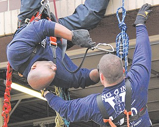 Youngstown firefighters Capt. Barry Finley, left, and Lt. Jamie Goodlet demonstrate a high-angle rescue Sunday.