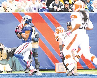New York Giants wide receiver Victor Cruz catches a touchdown pass in front of Cleveland Browns cornerback Trevin Wade (26) in the second half of Sunday's NFL game in East Rutherford, N.J. Cruz had a career-best three touchdown catches in the Giants' 41-27 win over the Browns.