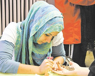 Lamia Sassya of Boardman draws henna art on hands during the Masjid Al-Khair mosque open house in Youngstown on Sunday.