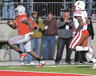 Ohio State quarterback Braxton Miller, left, scores a touchdown against Nebraska safety Daimion Staff ord during the second quarter of an NCAA game Saturday in Columbus. The Buckeyes won 63-38.