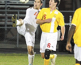 Howland's Jacob Froats (11) and Cardinal Mooney's Pat Price battle for the ball during Tuesday's soccer game in