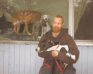 Michael Kelley, one of two people living at 2518 Hamilton St. SW, holds Oreo, one of the four dogs he and his girlfriend, Tiffany Charlton, keep at the home. The three others are shown behind him inside the house. The Warren Police Department and Warren Health Department ordered the house cleaned up and seven of the 11 dogs removed late last month because of conditions.