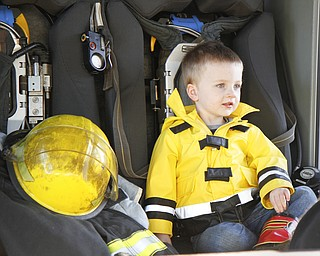 MADELYN P. HASTINGS | THE VINDICATOR  Landon Lovey, 2, of Hubbard, Ohio tests out a fire truck at the Hubbard fire open house while wearing his fire fighting jacket and boots. His father and grandfather are both firefighters.