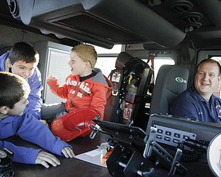 MADELYN P. HASTINGS | THE VINDICATOR  (L-R) Benjamin Wilcox, 7, Josh Wilcox, 10, Eli Barr, 5, and Eric Barr all from Hubbard, Ohio sit in a fire truck at the Hubbard fire open house on October 11, 2012.