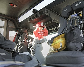 MADELYN P. HASTINGS | THE VINDICATOR  Eli Barr, 5, from Hubbard, Ohio sits in a fire truck tries on his firefighting helmet given to him at the Hubbard fire open house on October 11, 2012.