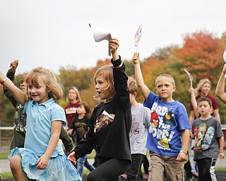 MADELYN P. HASTINGS   THE VINDICATOR  Students at EJ Blott Elementary walk the track of the Liberty Football field holding their decorated smiles during Smile Day. Smile Day was held to raise money for cleft palate surgeries of children in the area. One surgery costs $250 and the school raised $369.15 by collecting loose change from students and faculty.