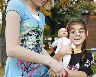 MADELYN P. HASTINGS   THE VINDICATOR  Serenity Sanders, 10, places a Smile Train bracelet on Carolynn Armstrong, 8, at EJ Blott Elementary during Smile Day. Smile Train is a non-profit organization that arranges programs worldwide such as Smile Day. Smile Day was held to raise money for cleft palate surgeries of children in the area. One surgery costs $250 and the school raised $369.15 by collecting loose change from students and faculty. Carolynn recently received the surgery.