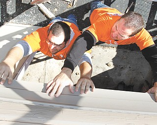 Home Depot volunteers Jason Weiser, left, of Boardman and Tim Hephner of Hermitage, Pa., install siding Thursday at the AMVETS Post 44 Career Center on Elm Street in Struthers. The project was financed by a $15,500 Home Depot grant.