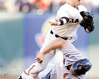 Giants second baseman Marco Scutaro grimaces as his leg is caught under sliding Cardinals baserunner Matt Holliday on a double play attempt Monday in San Francisco. The Giants won to even the National League Championship Series, 1-1.
