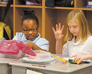 Amya Moody, left, and Antonia Wilson compare school supplies they received Thursday from the Association of Classified Employees at Youngstown State University. Sixty Kirkmere fourth- and fifth-graders received the items.