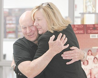 Struthers High basketball standout Bonnie Beachy receives a hug from her former coach, Dick Prest, during a visit to her alma mater Thursday. Beachy, who now lives in Texas, is battling cervical cancer for the second time with the intensity and fight that led her to a state championship (1978) and to being the Wildcats' all-time scoring leader (1,448 points).